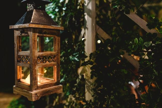 Drewniana latarnia oświetlająca noc w ogrodzie.