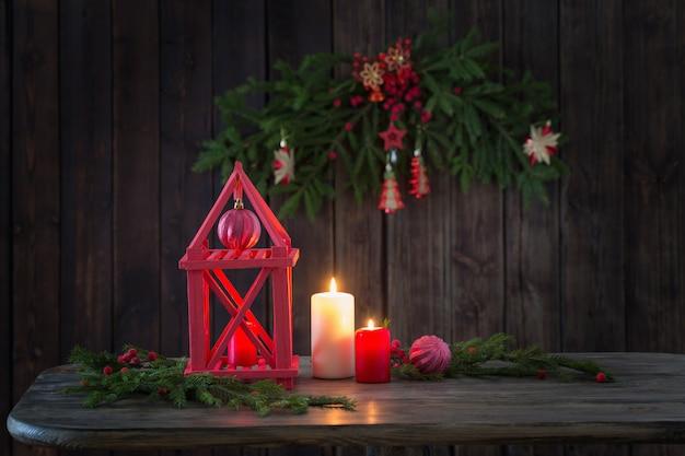 Drewniana latarnia ze świecami i christmas branchs na drewnie