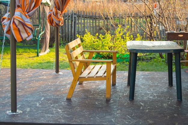 Drewniana ławka i plastikowy zielony stół na werandzie w wiejskim domu, wczesna wiosna, plener