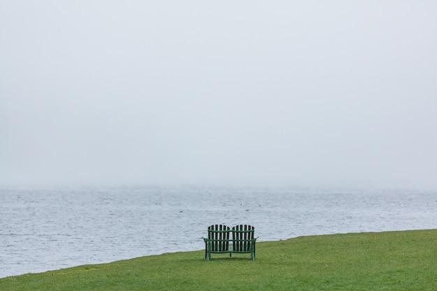 Drewniana ławka na pięknym zielonym brzegu jeziora