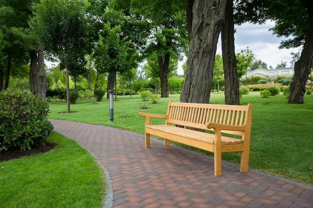 Drewniana ławka na ścieżce w pięknym parku