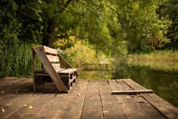 Drewniana ławka na tarasie nad jeziorem otoczonym zielenią