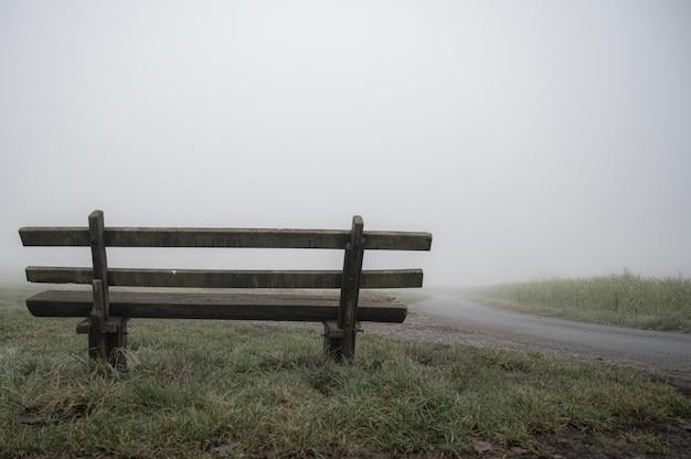 Drewniana ławka przy drodze pokrytej mgłą - koncepcja samotności