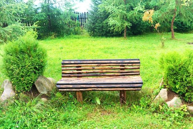 Drewniana ławka w zielonym parku. trawnik z zieloną trawą