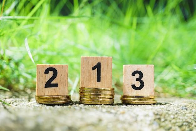 Drewniana liczba na złotych stert monetach z zielonym natury tłem