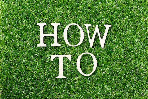 """Drewniana litera w słowie """"jak"""" na zielonej trawie"""