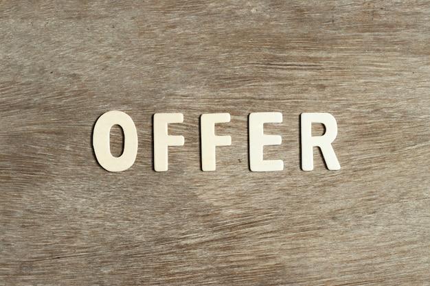 """Drewniana litera w słowie """"oferta"""" na płaskiej powierzchni drewnianej"""