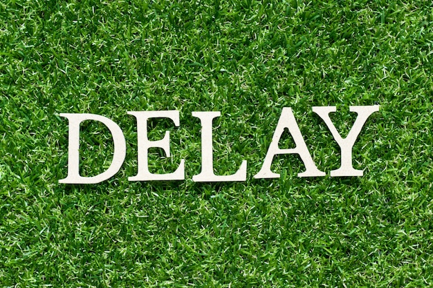 """Drewniana litera w słowie """"opóźnienie"""" na sztucznej zielonej trawie"""