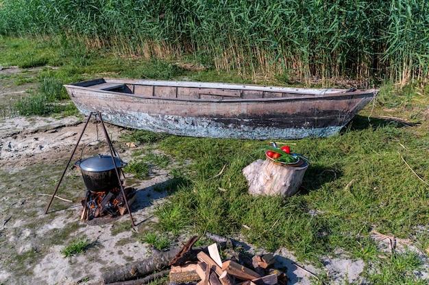 Drewniana łódka wędkarska na brzegu, melonik zawieszony nad ogniskiem i miska świeżych składników do zupy rybnej czekają na ugotowanie rybaka na otwartym ogniu.