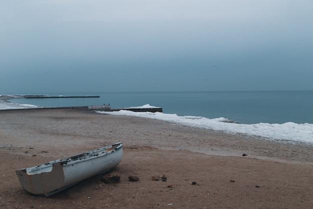 Drewniana łódź na brzegu morza zimą z morzem i błękitne niebo w tle