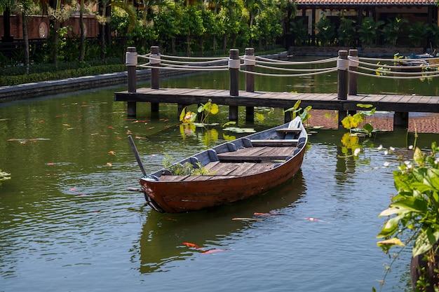 Drewniana łódź na stawie w pobliżu molo w tropikalnym ogrodzie w danang, wietnam
