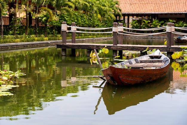 Drewniana łódź na stawie w pobliżu molo w tropikalnym ogrodzie w danang