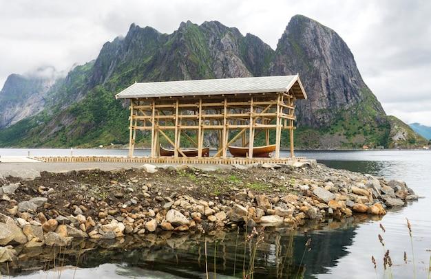 Drewniana łódź pod markizą na skalistym brzegu, archipelag lofoty, hrabstwo nordland, norwegia