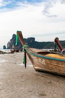 Drewniana łódź rybacka podczas odpływu siedziała na piaszczystym dnie oceanu.