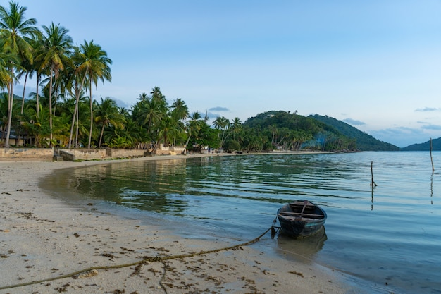 Drewniana łódź u wybrzeży tropikalnej wyspy. wieczór, zachód słońca w oceanie. tropikalny krajobraz. fale lekkie wstrząsają łodzią