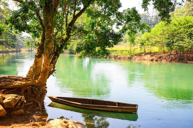 Drewniana łódź w pięknej zielonej rzece w gwatemali, ameryka środkowa