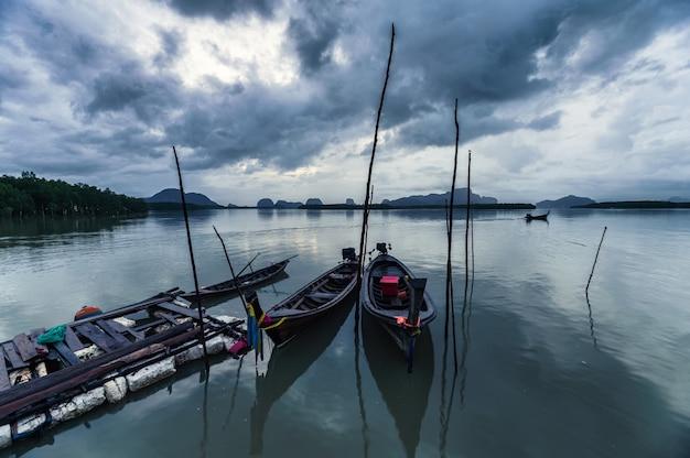 Drewniana łódź z długim ogonem zaparkowana w wiosce rybackiej w tropikalnym morzu w samchongtai, phang nga