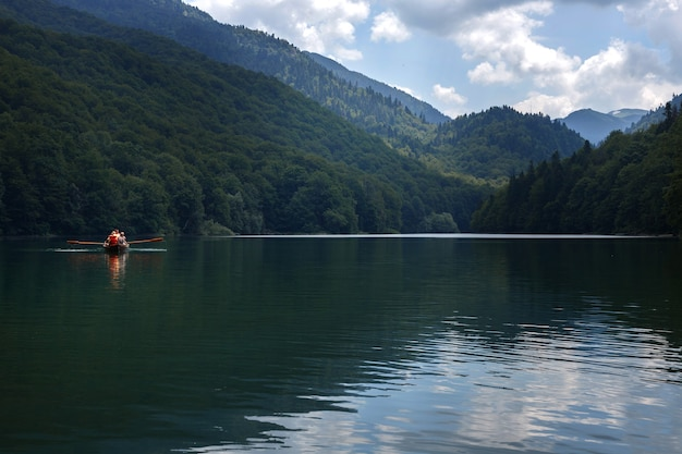 Drewniana łódź z turystami w podróży górskiego jeziora