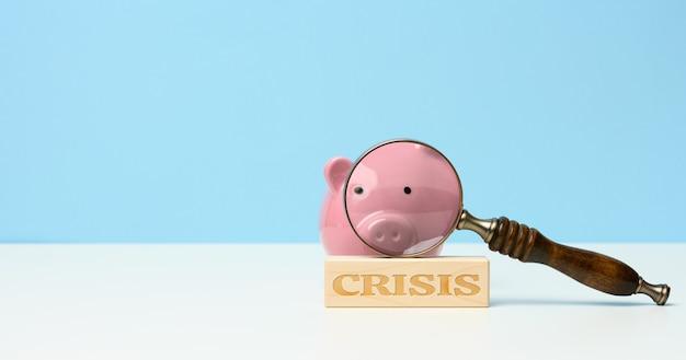 Drewniana lupa i różowa ceramiczna skarbonka, napis kryzys. analiza rynku papierów wartościowych, upadłości i braku pieniędzy. odpływ kapitału i depozytów z banków