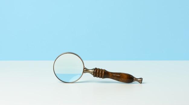 Drewniana lupa na białym tle. pojęcie niepewności i poszukiwanie rozwiązań, wątpliwości