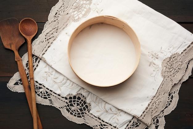 Drewniana łyżka i okrągłe sito leżą na białej serwetce