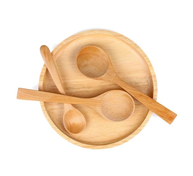 Drewniana łyżka i płyta drewniana na białym tle.