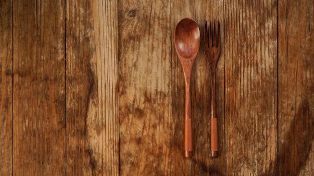 Drewniana łyżka i widelec na drewnianym tle. drewniane urządzenia w stylu azjatyckim. skopiuj miejsce