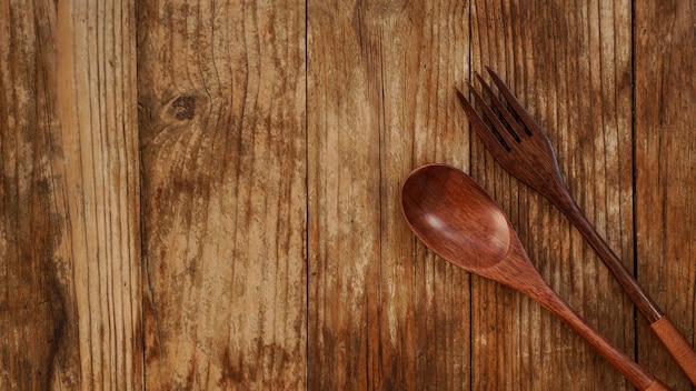 Drewniana łyżka i widelec na drewnianym tle. urządzenia drewniane w stylu azjatyckim