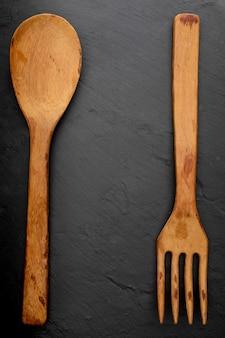 Drewniana łyżka i widelec na teksturowanej czarnej tablicy