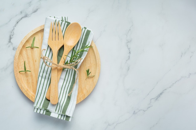 Drewniana łyżka i widelec z rozmarynem na drewnianym talerzu