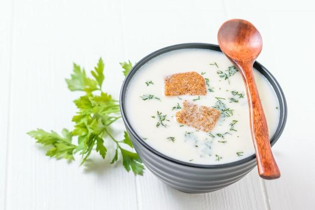 Drewniana łyżka na misce z kremową kalafiorową zupą na białym stole.