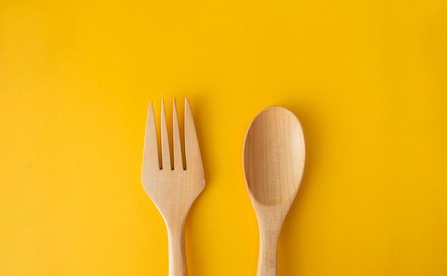 Drewniana łyżka na żółtej przestrzeni w koncepcji przestrzeni żywności