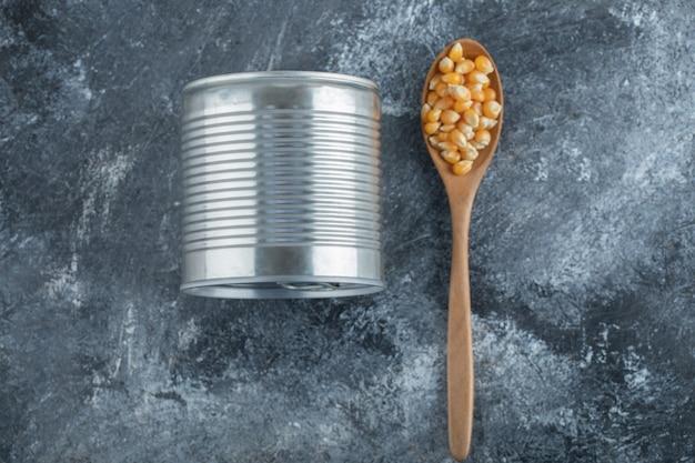 Drewniana łyżka pełna nasion popcornu z puszką.