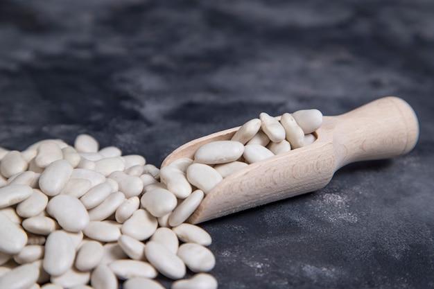 Drewniana łyżka pełna suchych ziaren masła umieszczonych na kamieniu
