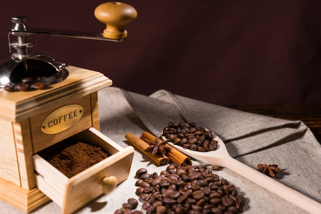 Drewniana łyżka trzyma ziarna kawy przez młynek
