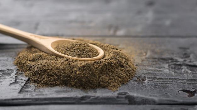 Drewniana łyżka z jasnego drewna w kupie zmielonego czarnego pieprzu