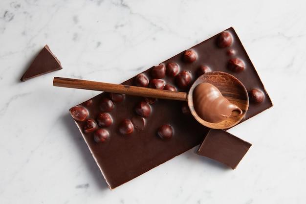Drewniana łyżka z karmelem na tabliczce czekolady na białym tle