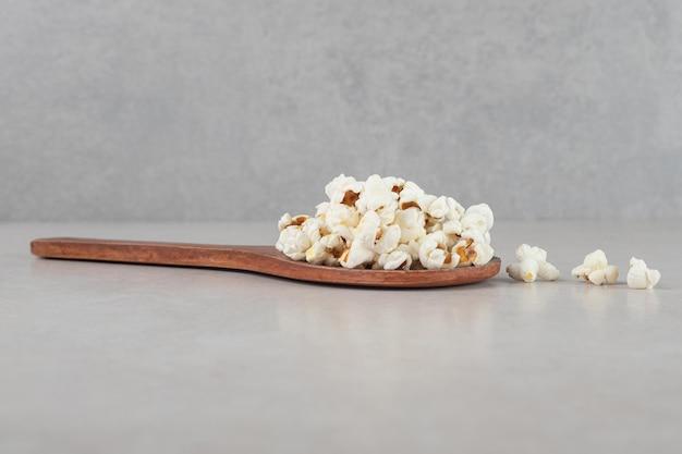 Drewniana łyżka z małym stosem popcornu na wierzchu na tle marmuru.