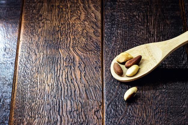 Drewniana łyżka z orzechami brazylijskimi, brazylijskimi orzechami używanymi do gotowania