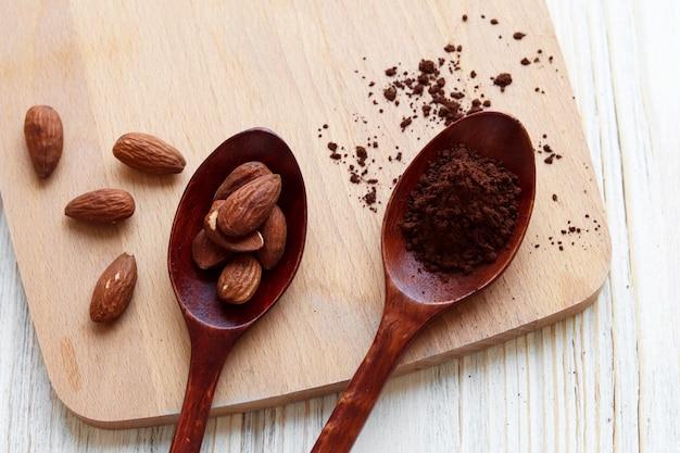 Drewniana łyżka z proszkiem kakaowym i drewniana łyżka z orzechami migdałowymi