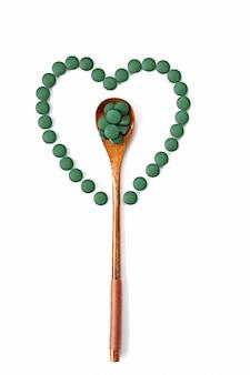 Drewniana łyżka z tabletkami spiruliny w środku serca okrągłych tabletek spiruliny