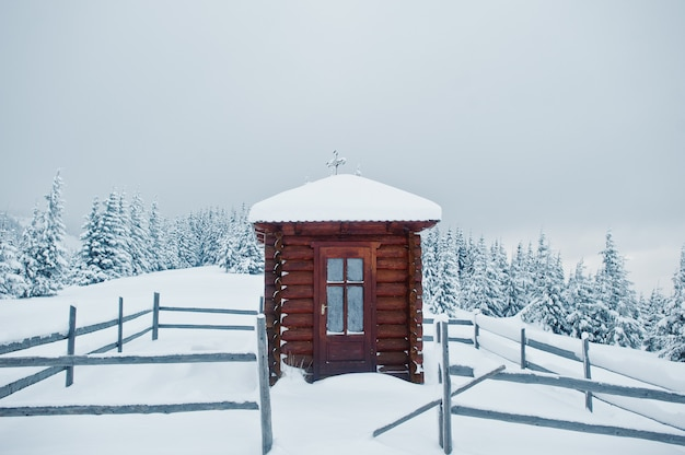 Drewniana mała kaplica kościelna w sosnach pokrytych śniegiem na górze chomiak, piękne zimowe krajobrazy karpat, ukraina, mróz przyroda,