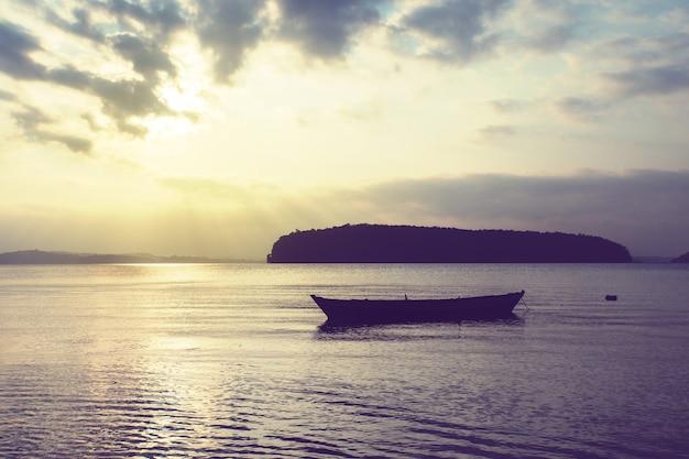Drewniana mała łódka na morzu na tle pięknego zachodu słońca na tropikalnej egzotycznej wyspie. spokojne morze. wioska łódź rybacka w indyjskiej prowincji. goa indie