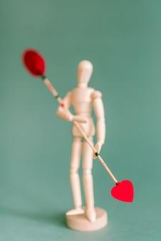 Drewniana mannequin mienia miłości strzała na zielonym stole
