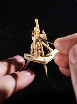 Drewniana miniatura skrzypiec na czarnym tle. proces rzemieślniczy, ręka rzemieślnika trzymająca narzędzie. makro