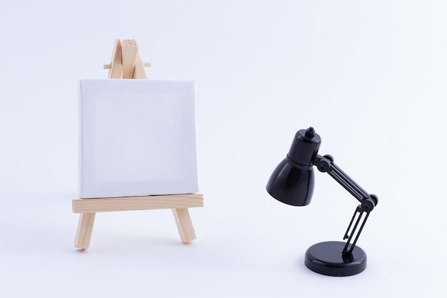 Drewniana miniatura sztalugi z pustym białym kwadratowym płótnem i lampą stołową