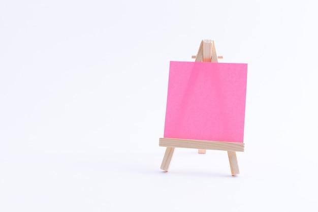 Drewniana miniatura sztalugi z pustym kolorowym kwadratowym płótnem lub papierem do notatek
