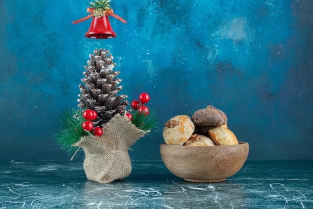 Drewniana miseczka słodkich ciasteczek ze świąteczną szyszką.