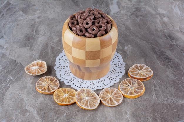 Drewniana miska czekoladowych krążków zbożowych z pokrojonymi w plasterki suszonymi owocami pomarańczy.