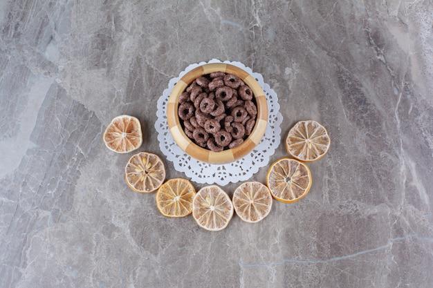 Drewniana miska czekoladowych płatków zbożowych z pokrojonymi w plasterki suszonymi owocami pomarańczy